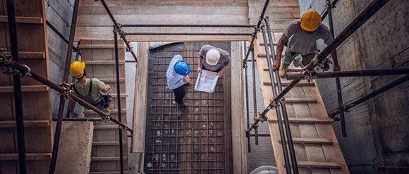 монтажники металлоконструкций на стройке дома